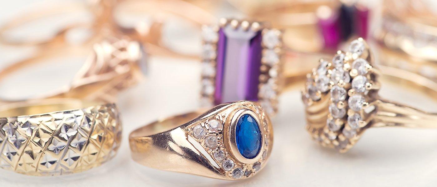 degli anelli dorati con diamanti e uno con una pietra blu al centro