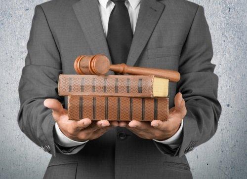 due mani che tengono due libri di legge e un martello di legno