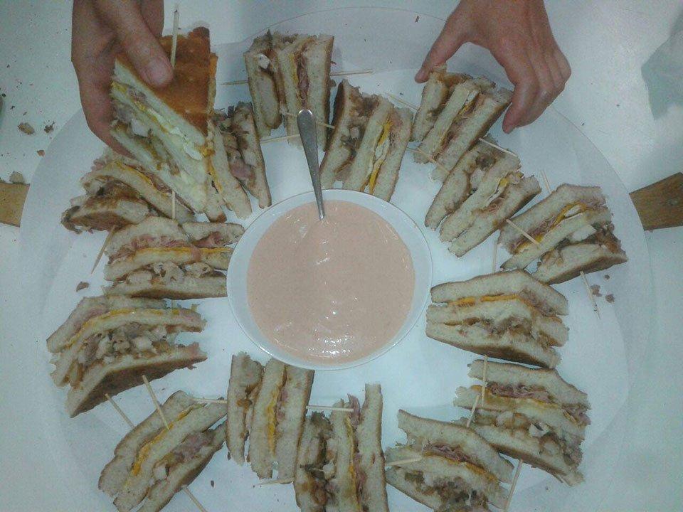 due mani con un piatto di tramezzini con al centro una ciotola con una salsa