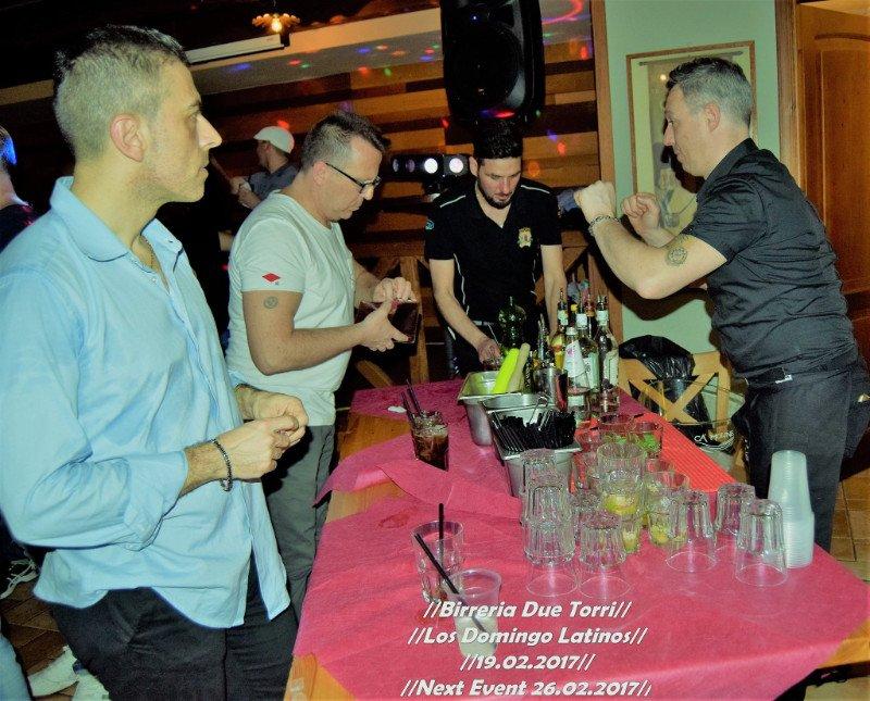 delle persone vicino a un tavolo con delle bottiglie e bicchieri di cocktail