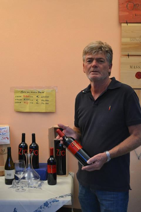 titolare azieda con una bottiglia di vino in mano