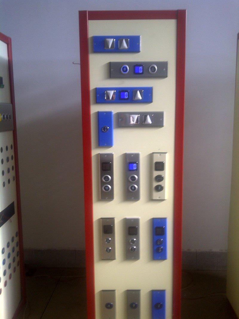 Serie di pulsantiere per ascensori in esposizione su un pannello di color bianco e rosso