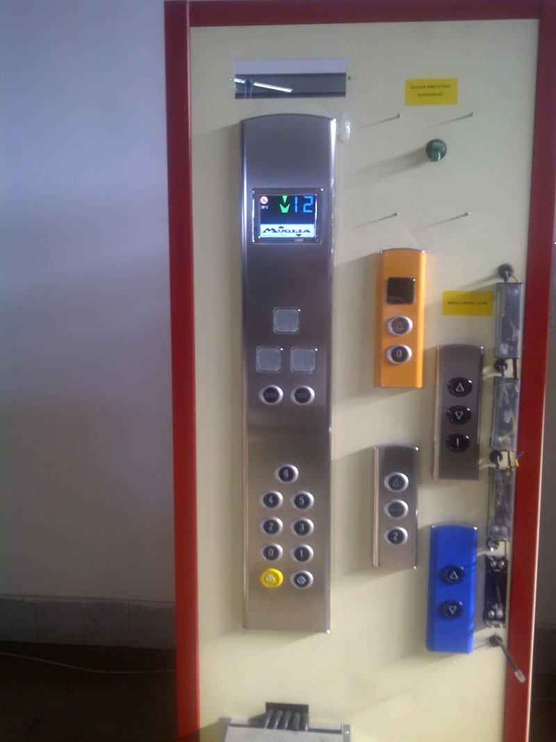 Pulsantiere per ascensori di diversi colori di cui una accesa e in funzione con il display che indica il dodicesimo piano