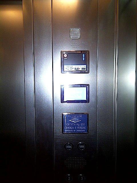 Vista di un display di un ascensore in metallo che indica la massima capienza di persone