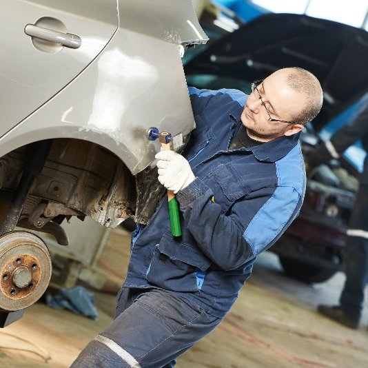 An auto body mechanic uses a hammer tool to repair the fender of a damaged car.