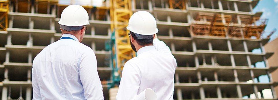 Persone con casco guardano casa in costruzione