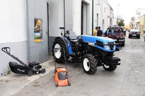 Piccolo trattore blu accantonate per la strada insieme a due macchine per tagliare erba: una piccola arancia e una grande nera