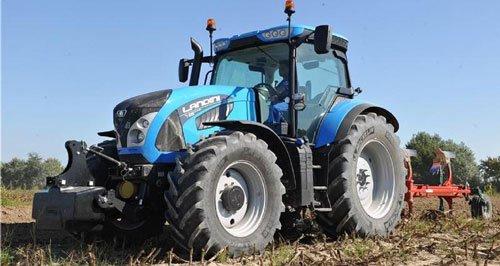 Grande trattore blu con apparecchiatura per il dissodamento e semina