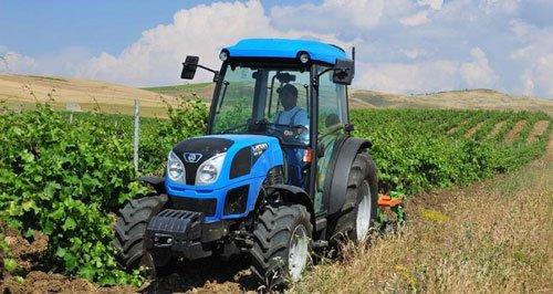 Trattore blu raccogliendo il raccolto