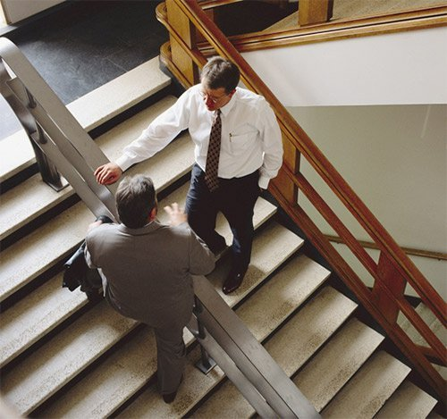 lawyers on office stairs having a discussion