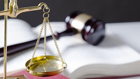 scale of justice and gavel on top of an open book