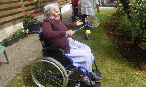 an elderly lady playing badminton