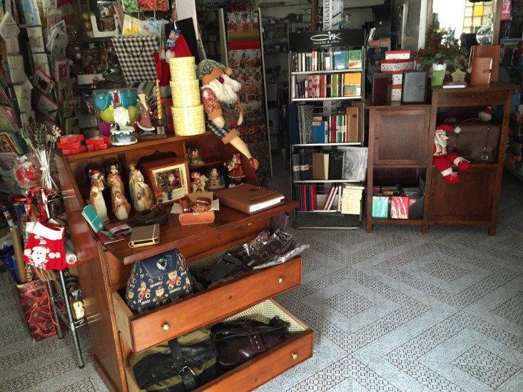 Mobile in legno con i cassetti aperti e pieni di muñecos, borsette....
