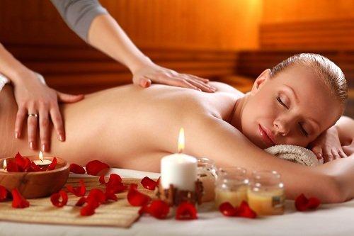 due mani che massaggiano la schiena di una donna bionda sdraiata