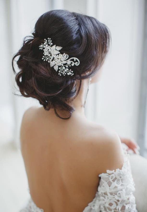 capelli raccolti tenuti da fermagio a fiori in morbida acconciatura da sposa
