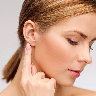 una donna che punta il dito sul suo orecchio