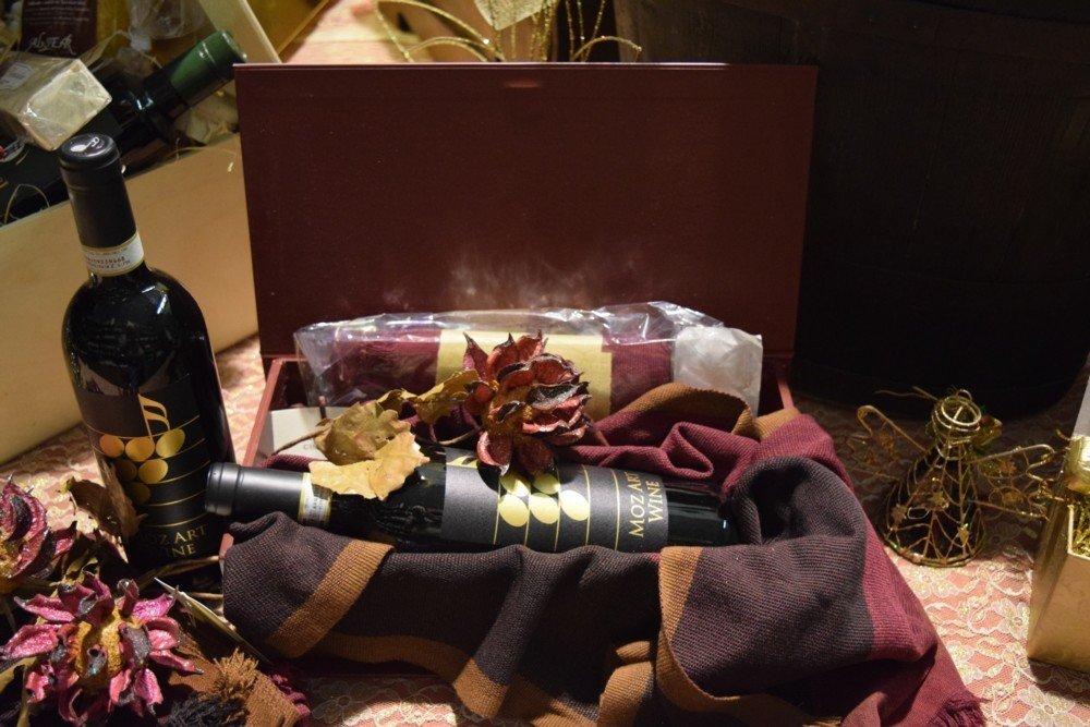 Scatola bordeaux con stola cachemire e bottiglia di Brunello di Montalcino