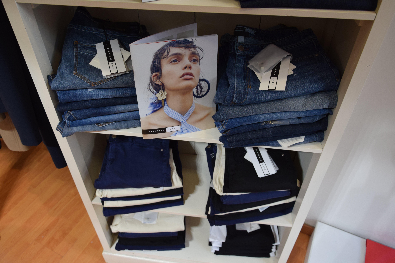 Tre mensole con jeans piegati e una brochure con scritto Sportmax Code