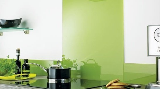Pans and herbs on a kitchen unit in front of a mint green and white perspex splashback