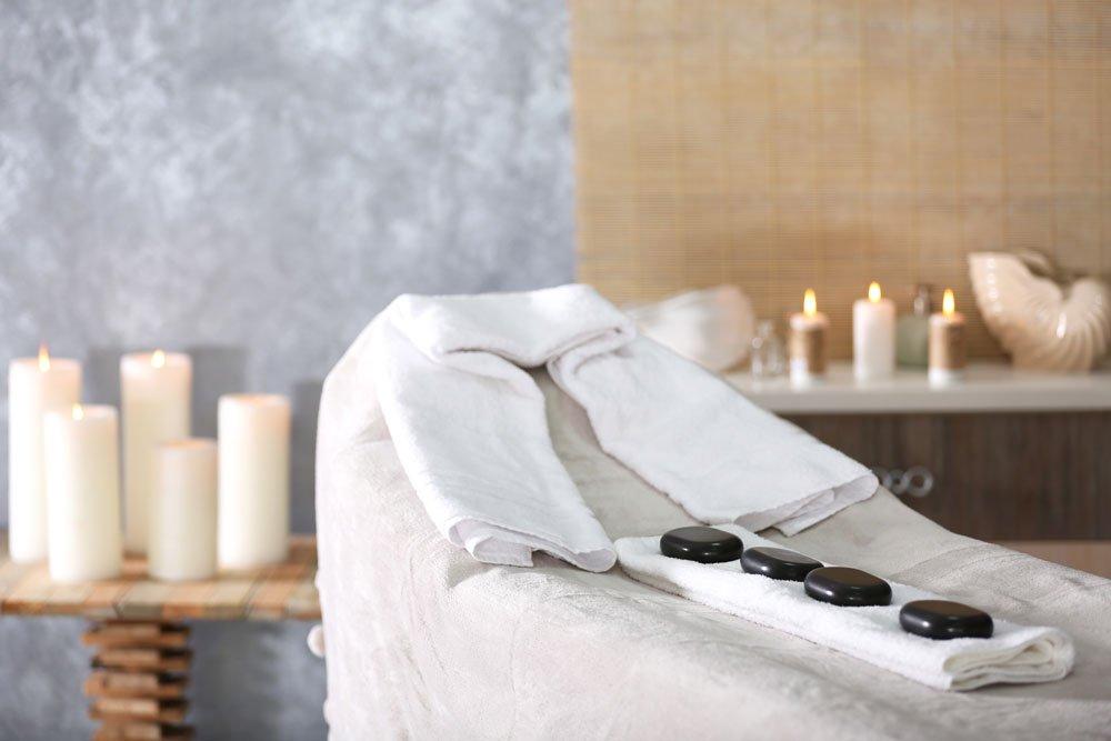 un lettino coperto di asciugamani con sopra delle pietre nere e dietro una serie di candele appoggiate su dei tavolini e su delle mensole