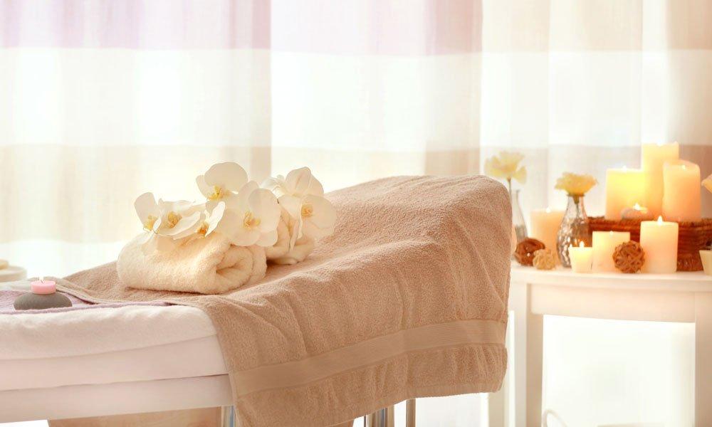 lettino con asciugamano, sopra pietre,fiori bianchi, olii d'essenza e candele