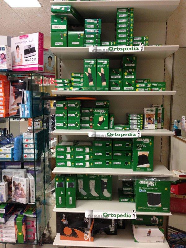delle mensole con delle scatole verdi di prodotti ortopedici e di fianco altre scatole di diversi colori