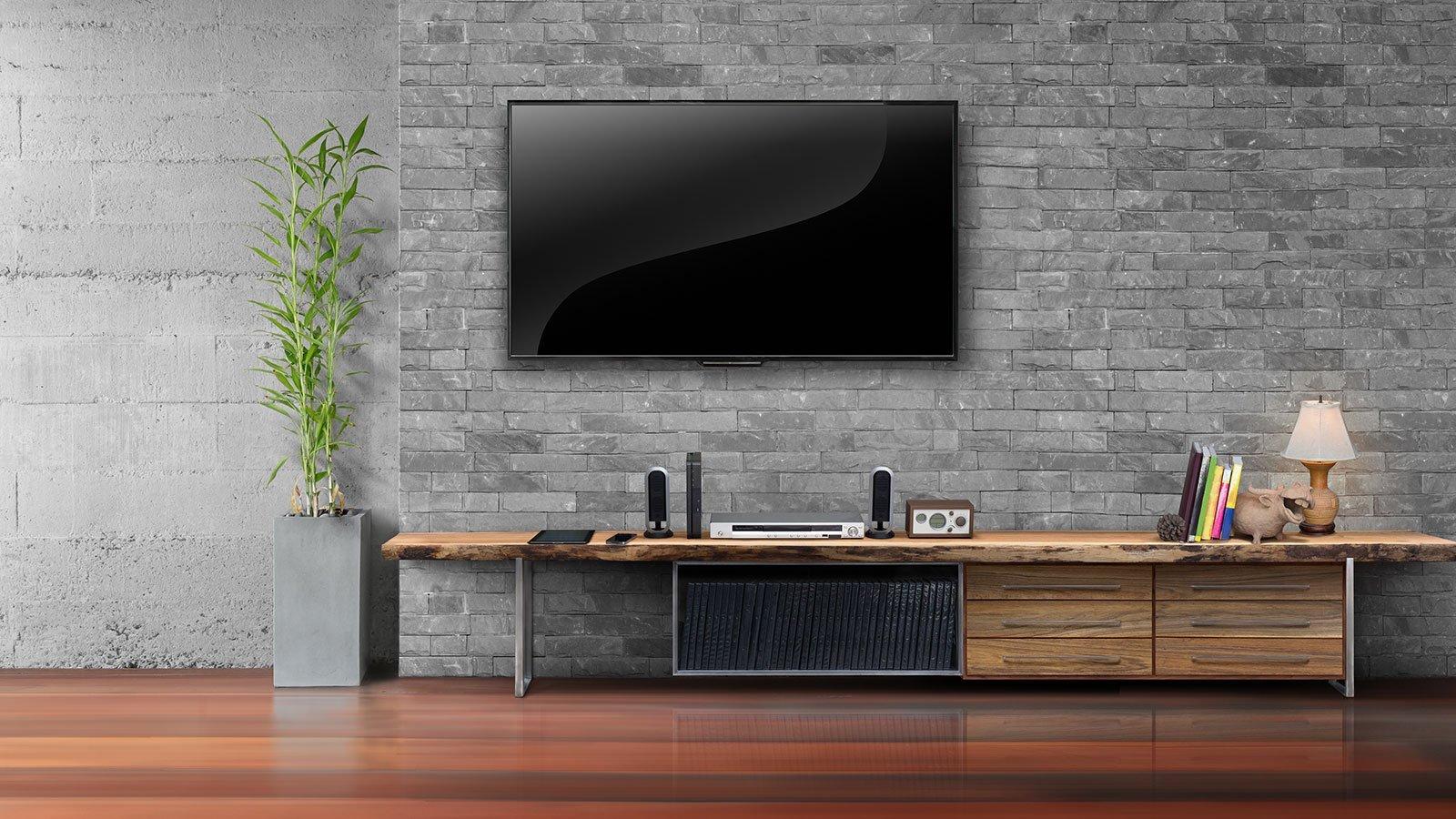 una TV a muro e sotto un mobile in legno