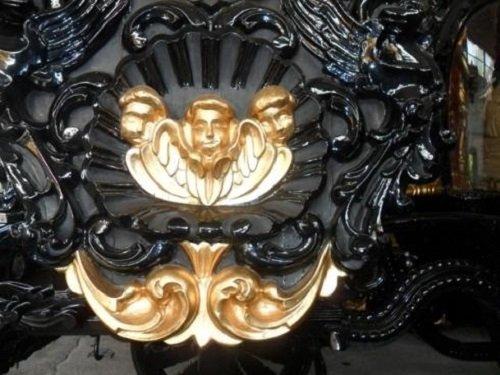tre statue raffiguranti dei volti dorati su una carrozza nera