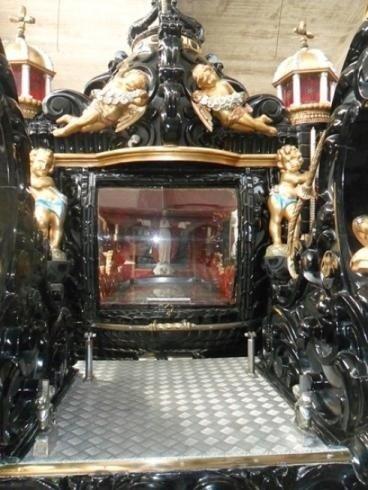 vista da fuori di una carrozza nera con delle statue