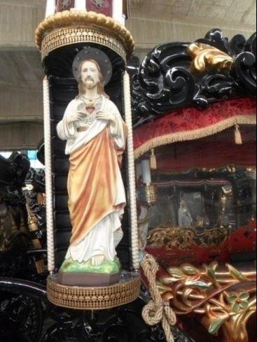 una statua di Gesù con un' aureola e delle candele