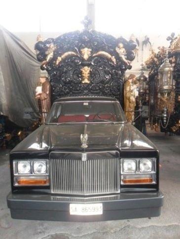un carro funebre e dietro una carrozza