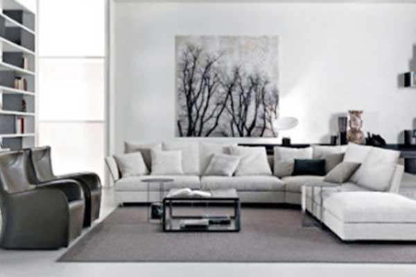 Una sala con mobili di colore bianco e nero, divano angolare, due poltrone di pelle sulla destra e al centro un tavolino
