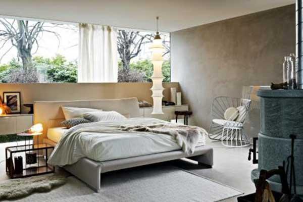 Una camera con letto di color beige, un mobile, dietro al muro delle cornici, una poltrona sul lato destro e un tavolino di cristallo sulla destra