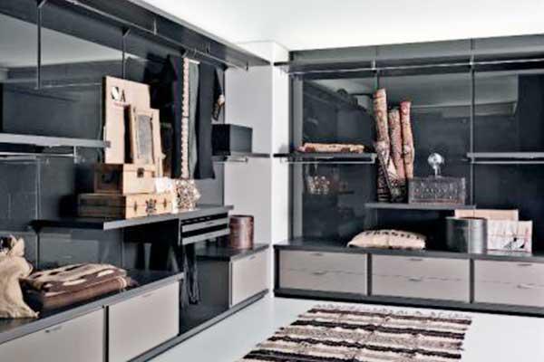 Una stanza con mobili di color grigio e nero al muro con dei cassetti, degli appendiabiti, e delle mensole con delle scatole