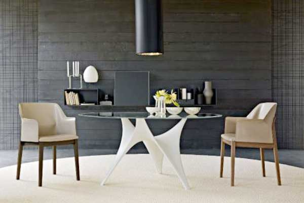 Una stanza con due poltrone,un tavolo di cristallo, lampada a sospensione, una mensola al muro con un applique, libri e altri oggetti