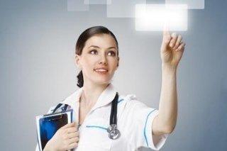 Una donna con un camice bianco che preme un'immagine digitale con un dito