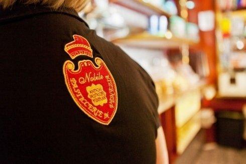 Un addetto della pasticceria indossa maglietta con il proprio logo