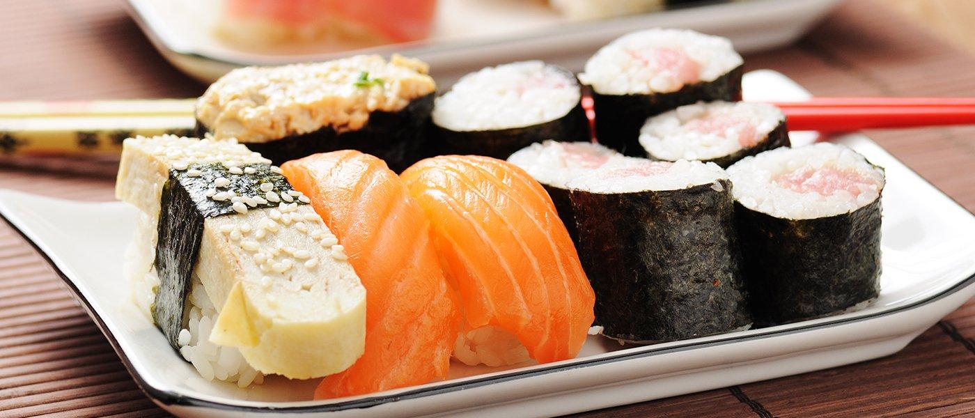 Un piatto con misto di sushi e bacchette di color rosso