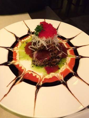 Un piatto a base di pesce con delle salse di color verde, rosa e salsa di soya