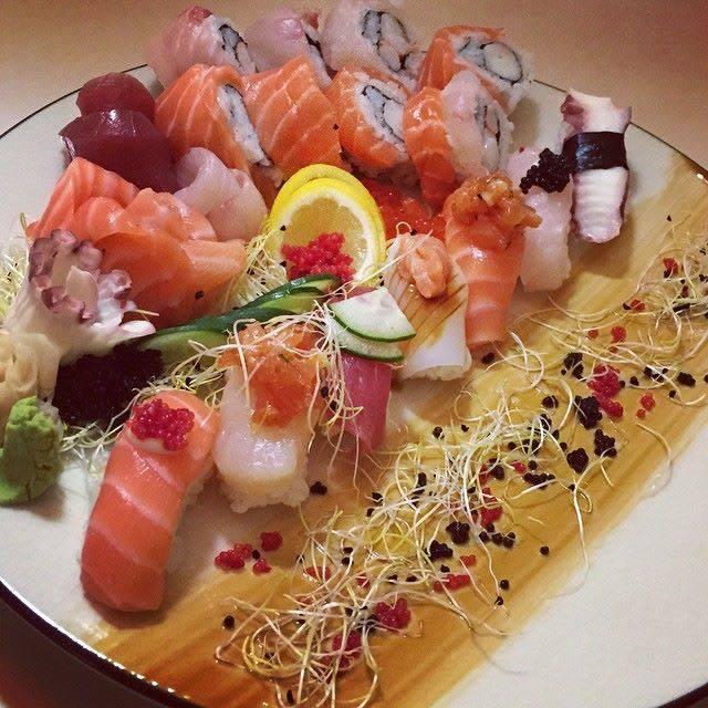 Un piatto con misto di sushi, germogli e fette di limone