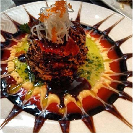 Un piatto a base di pesce con decorazione delle salse di colore verde, rosa e salsa di soya
