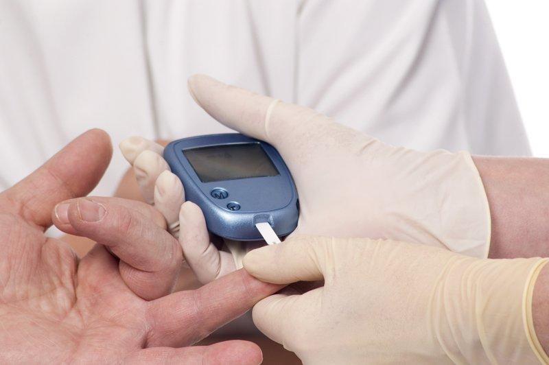 un dottore misura la glicemia al paziente