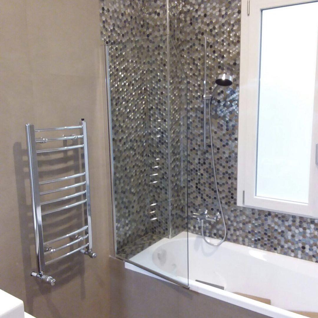 parete di doccia fatta di piccole piastrelle esagonali di colori marrone grigio e nero, scalda salviette