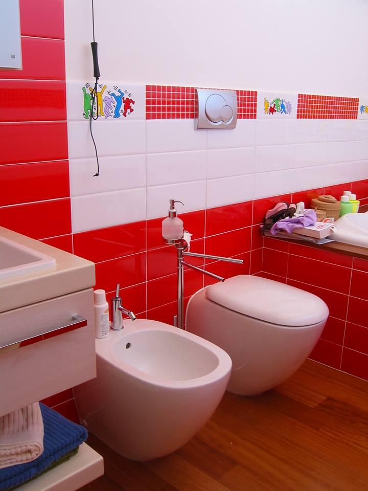 Bagno in piastrelle bianchi e rossi con piastrelle con bamboli di colori