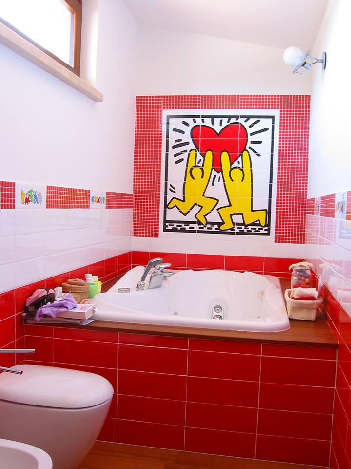 Parete rossa di piastrelle piccole, disegno di un grande cuore sorretto da due bamboli gialli