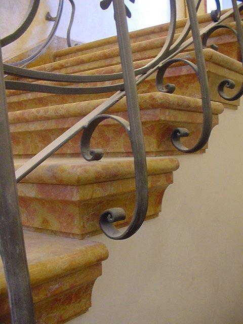 un corrimano in ferro e dei gradini in marmo nero
