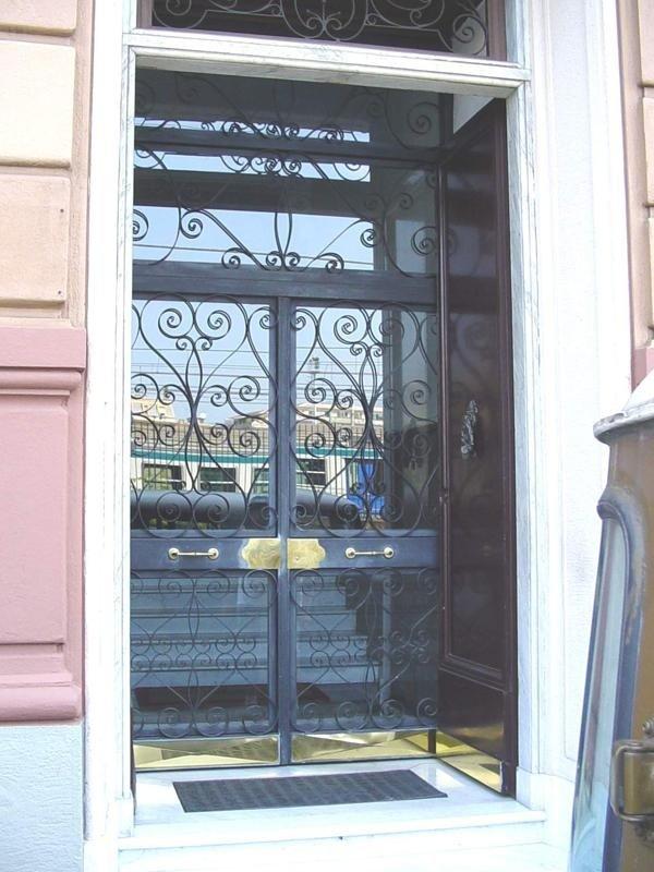 Portone in ferro a due ante con riccioli,fascione centrale,vasistas,fascioni inferiori in ottone
