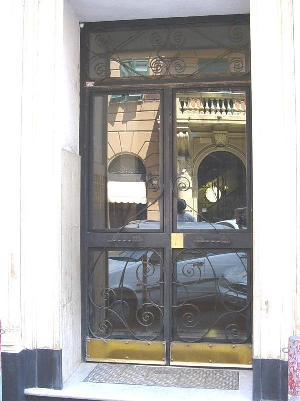 Portone in ferro a due ante con riccioli, fascione centrale,vasistas, fascioni inferiori in ottone