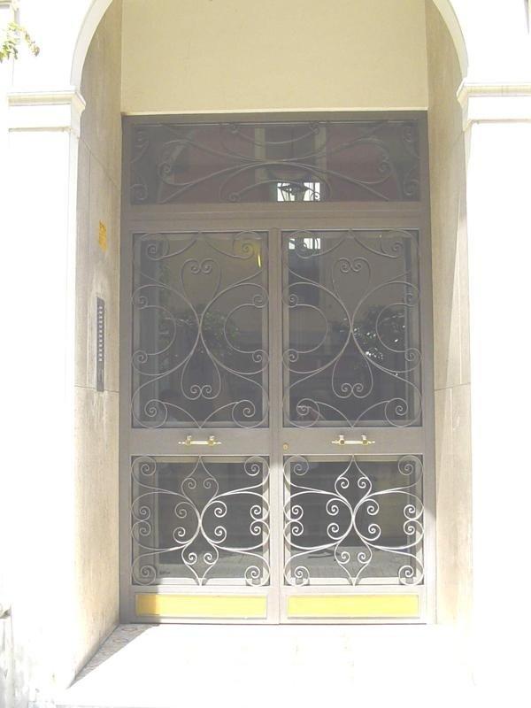 Portone in ferro a due ante con riccioli, fascione centrale, vasistas,fascioni inferiori in ottone e chiudiporta