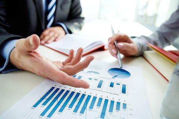 la mano di un uomo che gesticola alla scrivania con accanto un foglio raffigurante dei grafici e dall'altra parte un altro uomo con una penna in mano